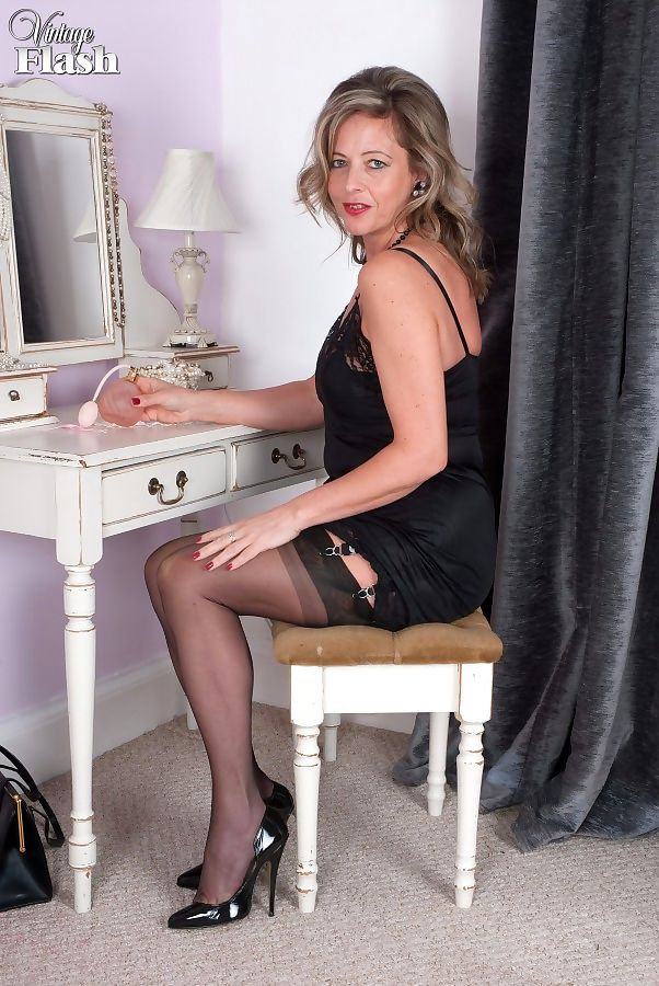 Classy older dame Silky strips to black nylons and garters at her vanity