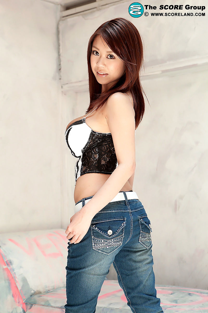 Asian model Ria Sakuragi holds her large tits in denim jeans and heels