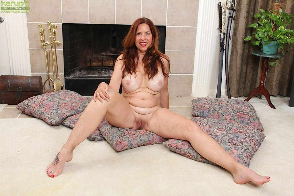 Amateur mature slut undressing to toy her hairy beaver by the fireplace