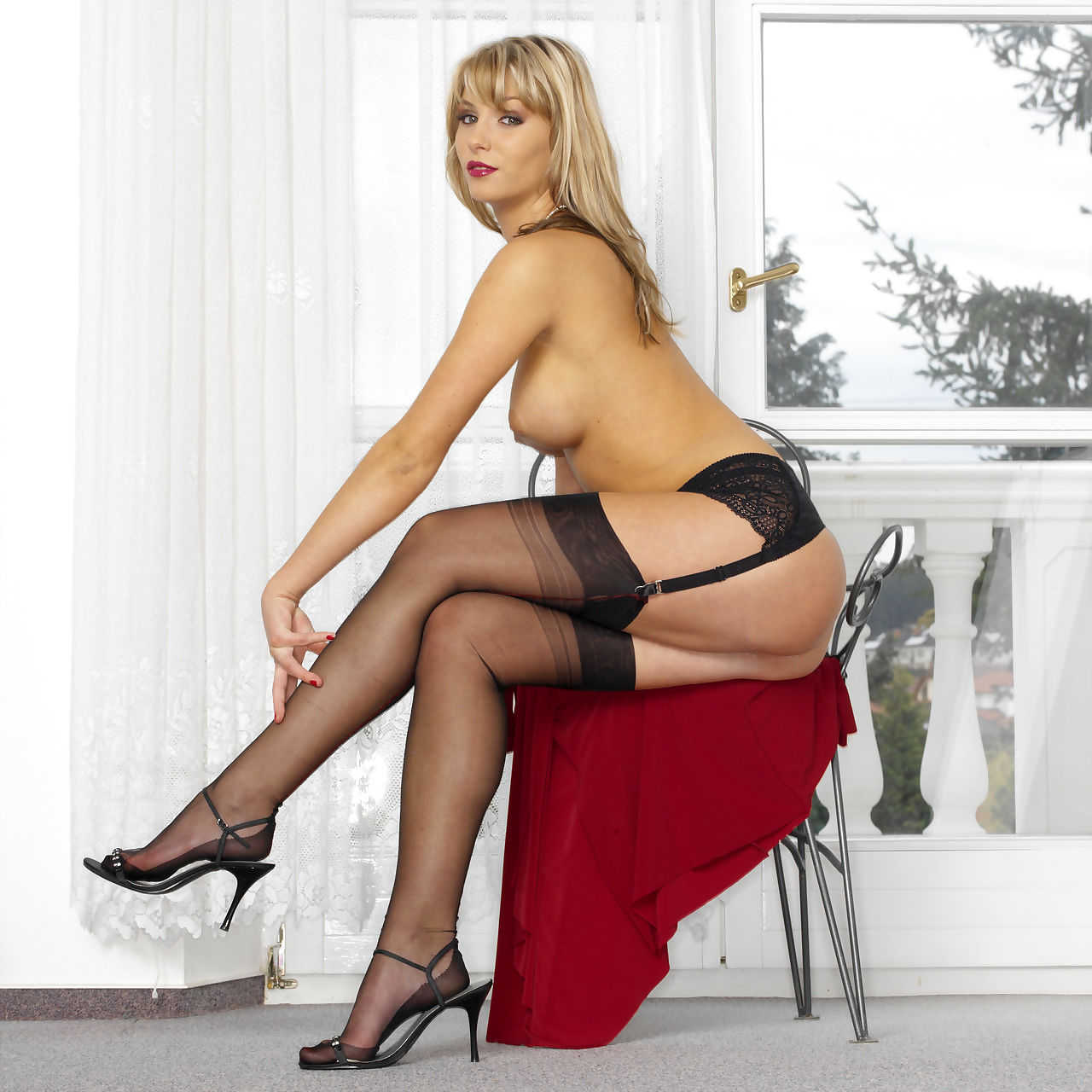 Sexy blonde model Sweet Denisa in black stockings posing topless on a chair
