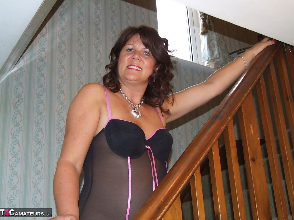 Busty horny housewife Sandy in sheer lingerie spreading pussy on the stairs
