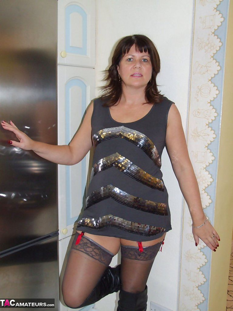 Naughty brunette amateur Sandy flashes her tits wearing stockings and boots