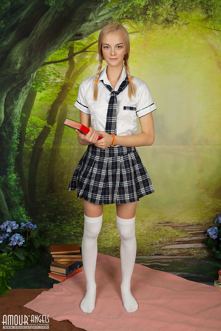 Young looking blonde Natasha removes school uniform to pose totally naked