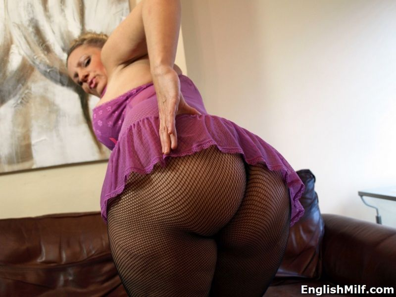 Hot mature Daniella English shows off her bald pussy in fishnet pantyhose