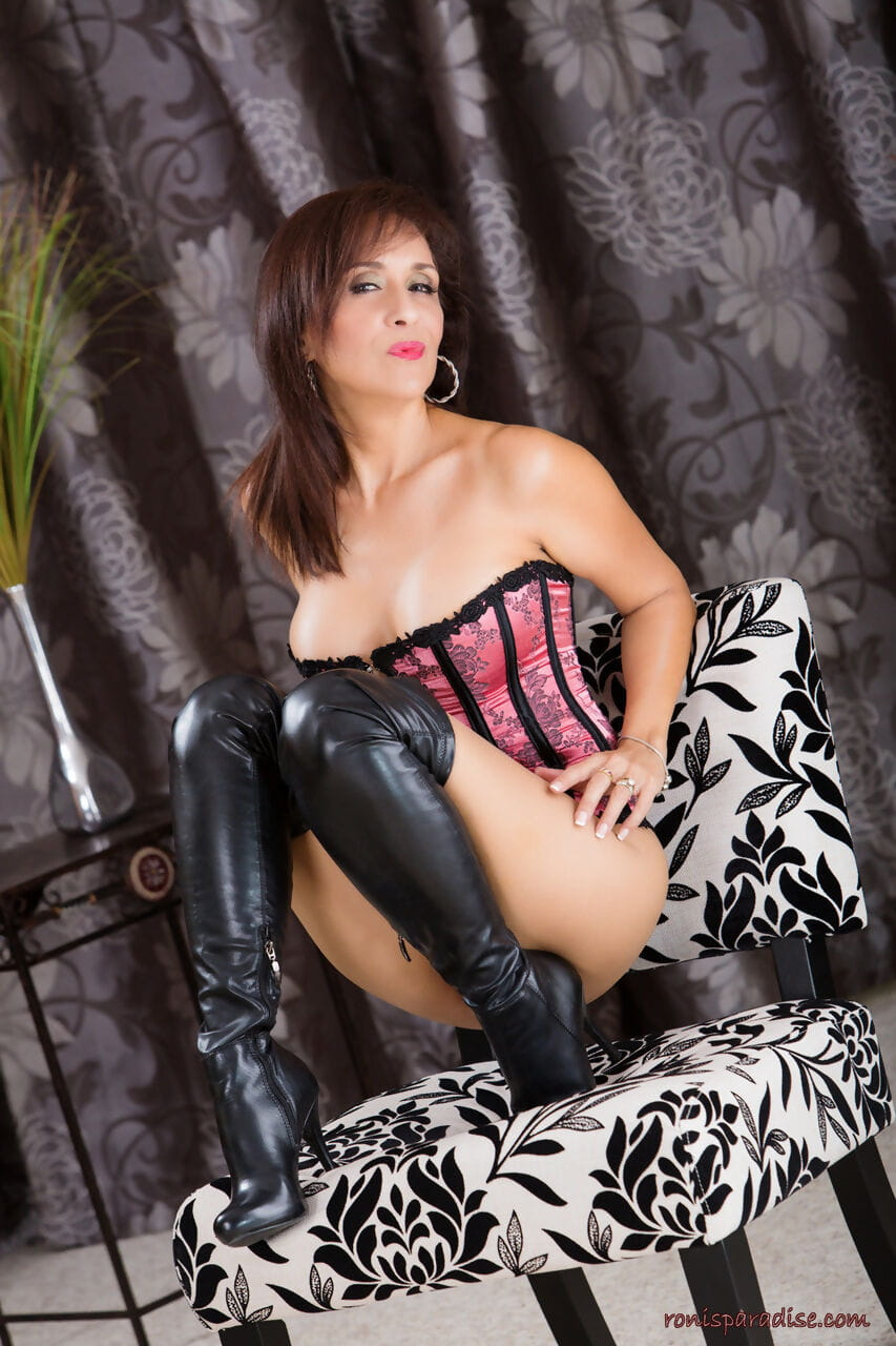 Hot mature woman Roni Ford models in long boots and hose with a bustier