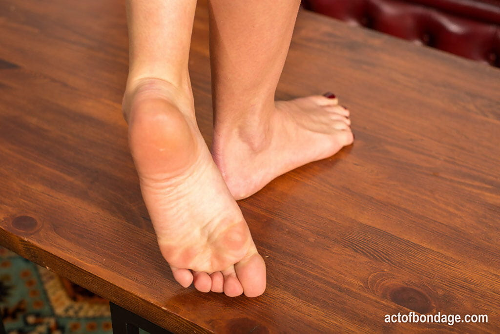 Naked girl displays the soles of her feet while tied up in bondage