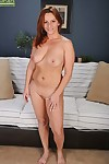 Redheaded MILF Gia Sophia stands naked after performing a striptease
