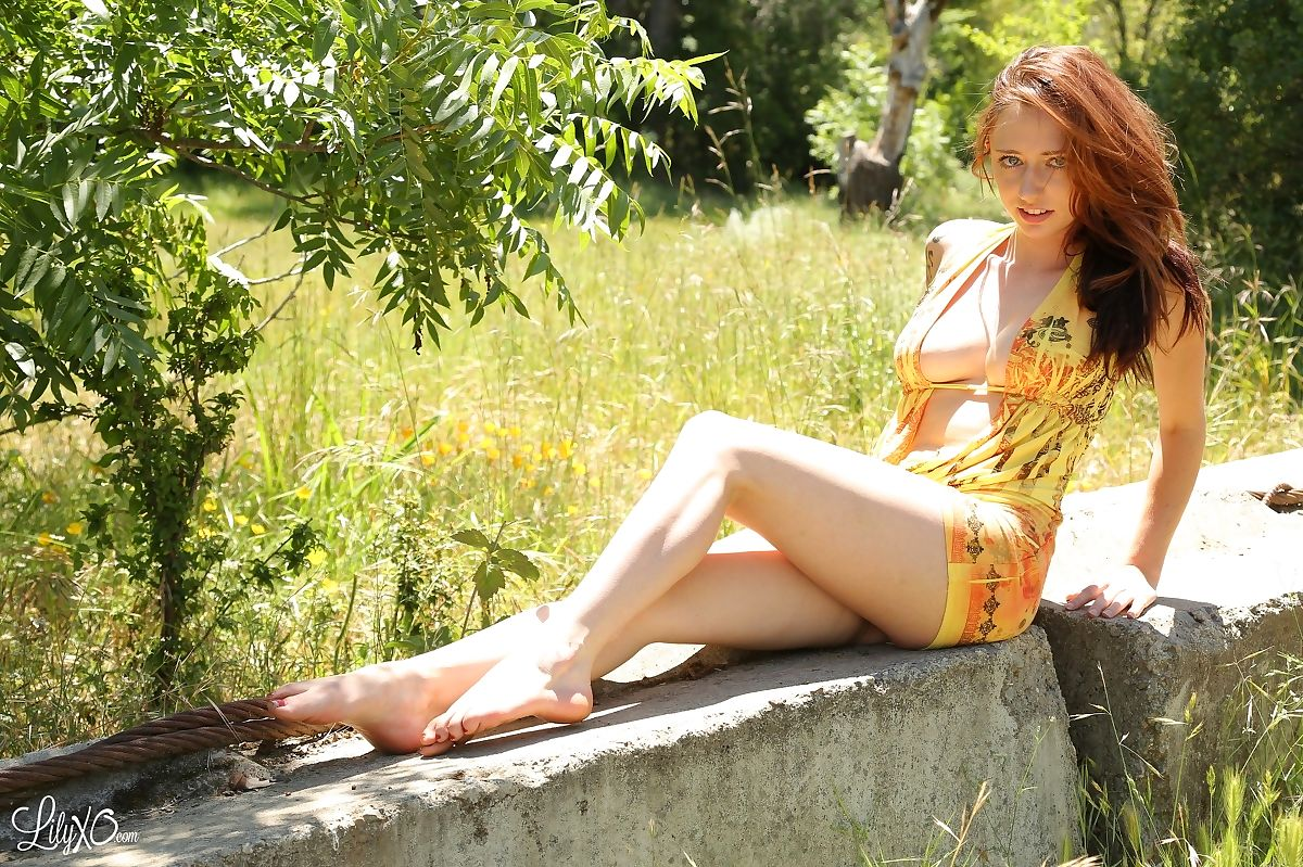 Pale redhead Lily Xo models bottomless outdoors in bare feet on concrete bench