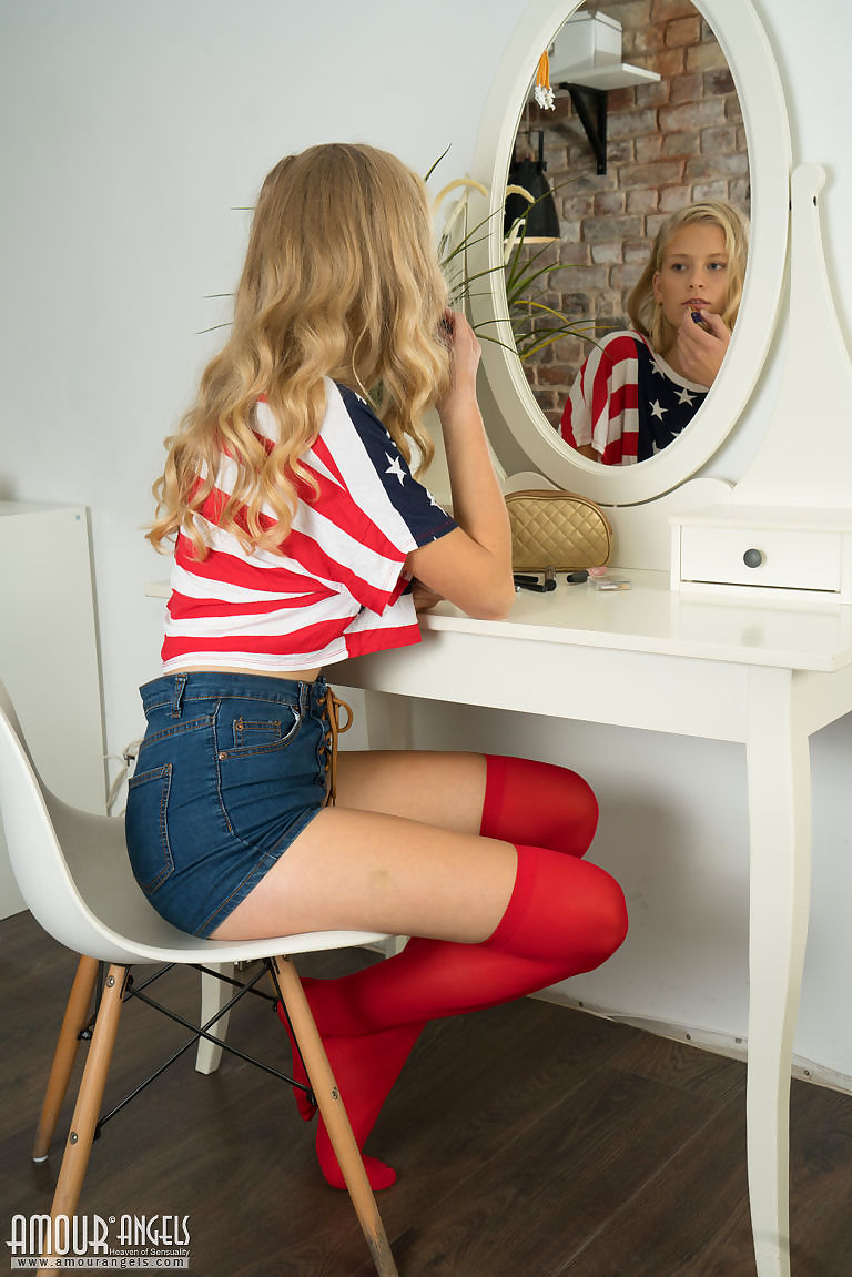 Slim blonde teen Amy rolls off red OTK socks to finish getting naked