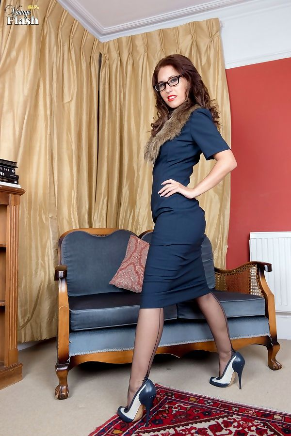 Nerdy woman Jess West undoes her garters to finish getting naked in glasses