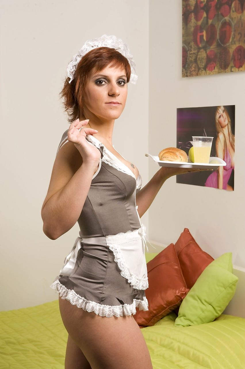 Redheaded house maid takes off her uniform to model in the nude